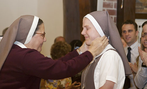 After vesting with the full habit, Sister Molly Joyce of the Merciful Heart of Jesus receives a crucifix from Sister Ana Margarita Lanzas.