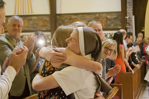 After vesting with the full habit, Sister Molly Joyce of the Merciful Heart of Jesus hugs a member of her family.