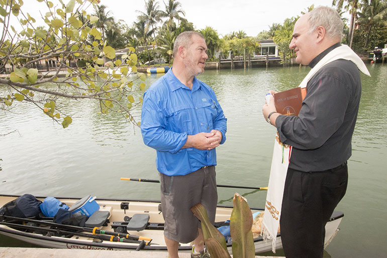 Father Roberto Cid, pastor of St. Patrick Church, Miami Beach, speaks with Greg Dougherty, who is embarking on a 1,400-mile sea journey from Miami to New York.