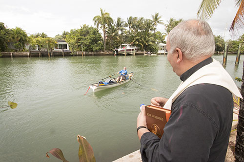 Father Roberto Cid, pastor of St. Patrick, Miami Beach, watches as Greg Dougherty sets off from a canal that runs behind the church on the first day of his 1,400-mile sea journey from Miami to New York.