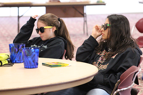 We all wear shades sometimes: With sunglasses on, Karina Czubkowski and Stephanie Melendez listen to a presentation on perspective.