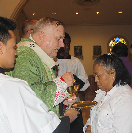 Guadalupe Hernández, a domestic worker, receives Communion from Archbishop Thomas Wenski during the Mass recognizing their important work, June 25 at St. Mary Cathedral.