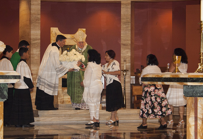 Representatives of Women Working Together USA take up a basket of white flowers as part of the offertory. The flowers bore a ribbon with the names of loved ones who have died or could not be present at the Mass in honor of domestic workers, most of whom are women and immigrants.