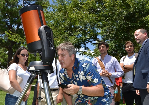 Professor David Quesada resets the telescope to follow the track of the sun as the moon eclipses it.