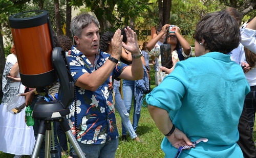David Quesada, associate professor of natural science at St. Thomas University, explains the eclipse viewing to Ana Rodriguez-Soto, editor of The Florida Catholic.