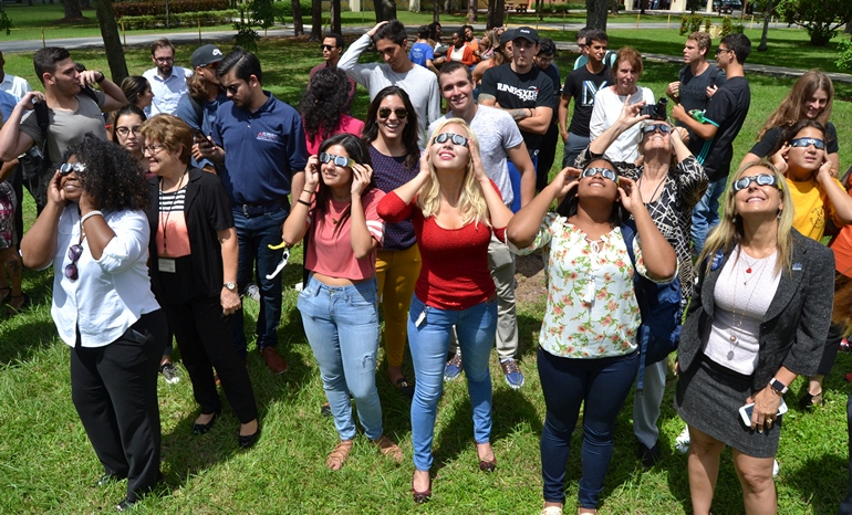 Students, staff and faculty at St. Thomas University gaze at the solar eclipse through special glasses.