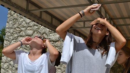 Nursing students Katerina Alvarez, left, and Daniella Piloto gaze sunward during the solar eclipse over St. Thomas University.