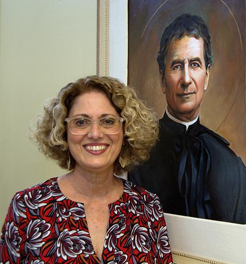 Berta Cabrera, executive director of St. John Bosco Clinic, shows a painting of the 19th century Italian saint.