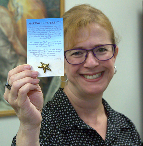 Luz Gallardo, supervisor at St. John Bosco Clinic, shows a starfish pin given out to all the clinic volunteers. The starfish parable illustrates how one person may not solve a problem but can still make a difference.