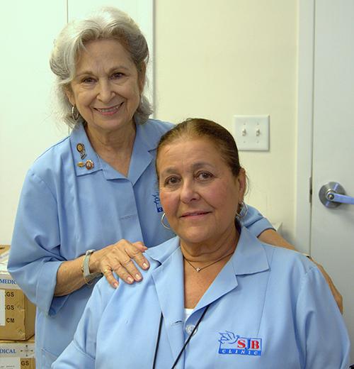 Ady Viera, standing, with fellow volunteer Teresita Michelena at St. John Bosco Clinic.