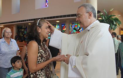 Ada Luz Maradiaga,  feligresa de ST. Martha, en Miami Shores recibe la bendición de Mons. Rodrigo Urbina, párroco de la Basílica Inmaculada Concepción de El Viejo, Nicaragua.