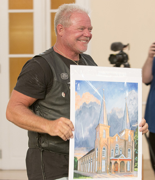 """Bear Woznick shows off the souvenir he received during his stop at the Basilica of St. Mary Star of the Sea. Archbishop Thomas Wenski's motorcycle ride to Key West will be featured in the second season of Woznick's """"Long Ride Home"""" reality series on EWTN."""