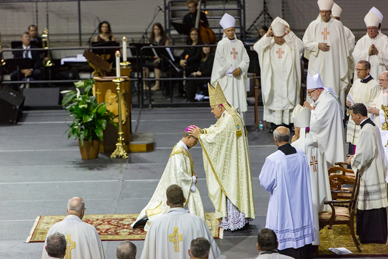 Archbishop Thomas Wenski lays hands over Bishop-elect William Wack, ordaining him to the episcopacy. Thousands of the faithful gathered at the Pensacola Bay Center Aug. 22, while others watched worldwide via the web, the ordination and installation of the sixth bishop of Pensacola-Tallahassee, Bishop William A. Wack, a member of the Congregation of Holy Cross.