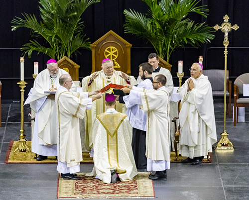 Two deacons, standing at either side, hold the Book of the Gospels above Bishop-elect William Wack's head as Archbishop Thomas Wenski recites the prayer of consecration. Archbishop Wenski was the principal consecrator, with co-consecrators Bishop Joe S. Vasquez of Austin and Bishop Daniel R. Jenky, Congregation of Holy Cross, of Peoria.