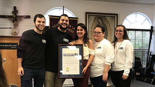 Happy Encuentros Juveniles Day! Encuentros Juveniles leaders, including Carlos San Jose, Mark Gomez, Rebecca Garcia, Sophia Bello Diaz and Sabita Perez pose with a framed proclamation presented by Miami Dade County Commissioner Esteban Bovo, Jr., declaring July 21 as Encuentros Juveniles Day in Miami Dade County.