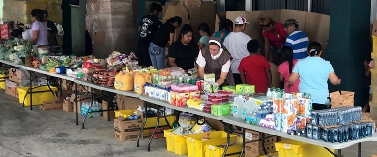 Parishioners and Servants of the Pierced Hearts of Jesus and Mary prepare a food distribution at San Juan Chapel in Florida City.