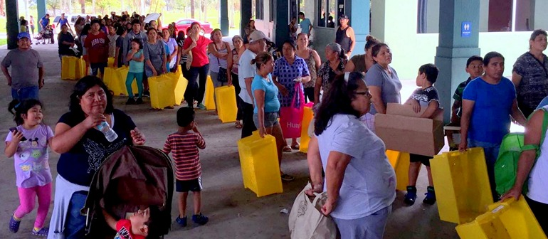 Parishioners line up for food distribution at San Juan Chapel in Florida City.