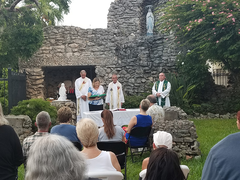 A parishioner proclaims one of the readings as Father John Baker, center, accompanied by Deacon Peter Batty, left, and Father Juan Rumin Dominguez, right, celebrates 7 a.m. Mass Sept. 7 at the grotto of Our Lady of Lourdes outside the Basilica of St. Mary Star of the Sea.