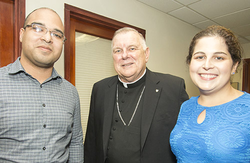 Archbishop Thomas Wenski poses with Catholic Legal Services' attorneys Felix Montañez and Kristie-Anne Padron during a visit to the agency's downtown office Sept. 27 to kick off the Share the Journey campaign.