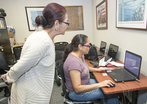 Esperanza Montaldo, a citizenship accredited representative with Catholic Legal Services, watches as client Sonia Hernandez fills out the application for U.S. citizenship at the agency's downtown Miami office.