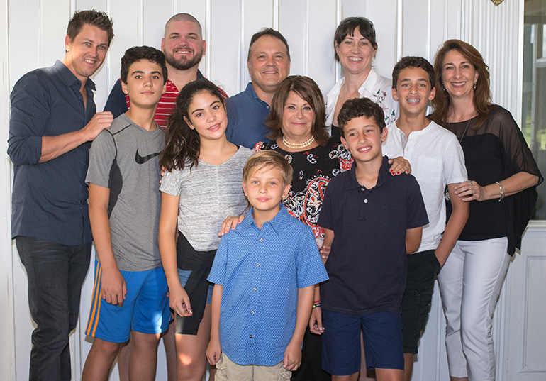 Margaret Barbick, center, second row, is surrounded by former students at a farewell party held to mark her retirement in June of this year. From left: Michael Longman ('82-'83), Rocco Marando, 13, Danny Scott ('94), Gianna Marando, 11, Rocky Marando ('75-'76), Rosemarie Banich ('75-'76), Nico Pacheco, 11, Sixto Pacheco, 13, Anne Mennes ('75-'76), and Tristan Longman, 9 (in front).