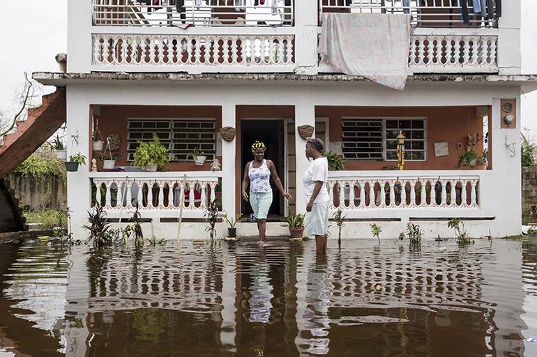 Los residentes de la localidad puertorriqueña de Loíza se enfrentan a las calles inundadas tras el azote del huracán María, el 22 de septiembre.