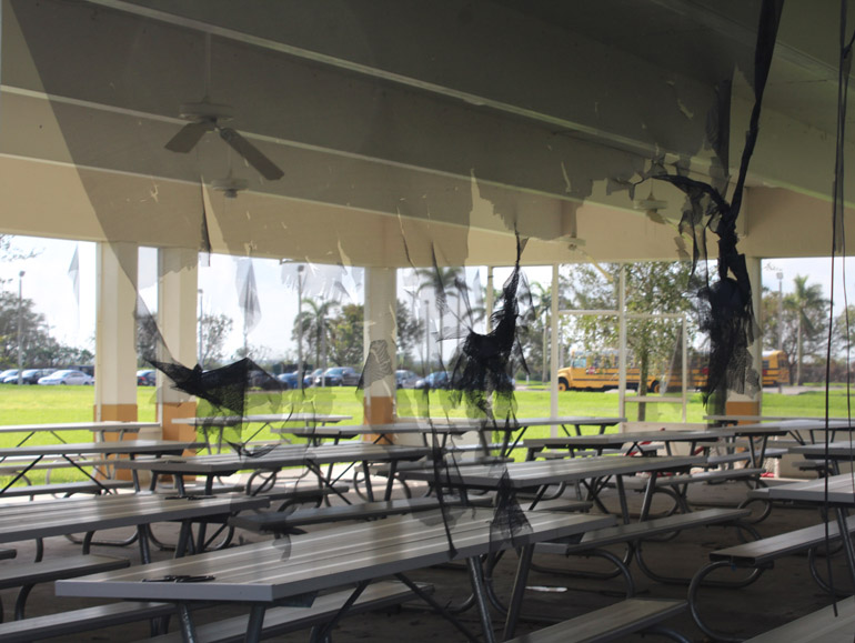 Shredded screen windows and doors, as well as dangling ceiling fans, provide an eerie ambience to the outdoor dining pavilion where many students eat lunch.