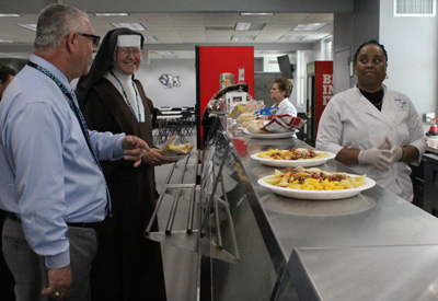Filippo Baglio, director of operations at Archbishop Coleman Carroll and a native Italian, teases Sister Margaret Ann for not choosing the pasta for lunch.