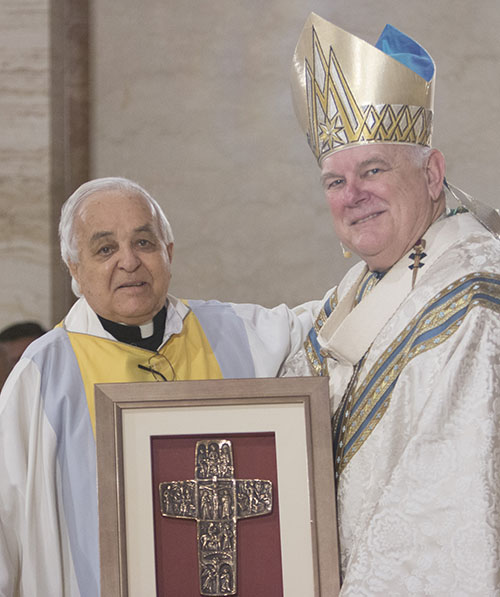 Archbishop Thomas Wenski congratulates Father Hernando Villegas on his 60th anniversary in the priesthood during the chrism Mass this past April.