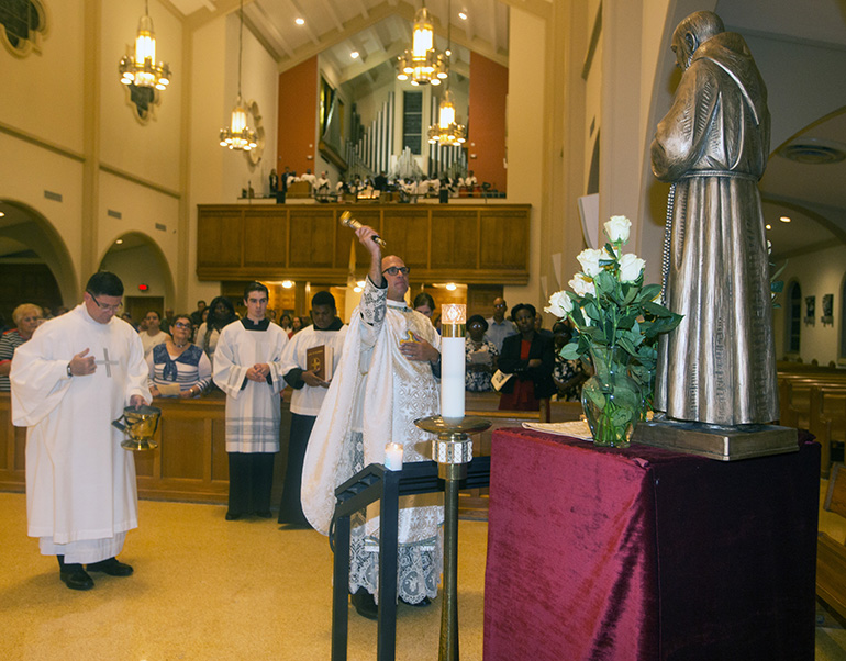Father Christopher Marino blesses the statue of St. Padre Pio which was donated to St. Mary Cathedral.