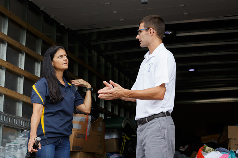 Robert Wright, principal of the Basilica School of St. Mary Star of the Sea in Key West, speaks with Kathy Mesa, a member of St. John Neumann Parish in Miami. She was one of the volunteers from the archdiocese who delivered a caravan of emergency supplies Sept. 26 to locations throughout the Florida Keys as that region recovers from Hurricane Irma. The donated items had been collected at a dozen Catholic schools and parishes in Miami following the storm and left at hard-hit sites from Key Largo to Key West.