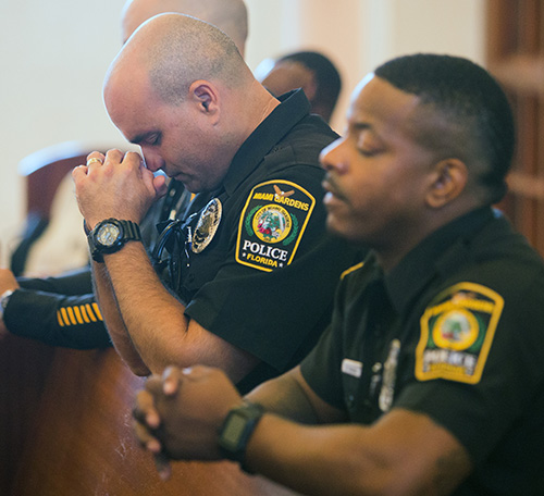 Miami Gardens police officers Carlos Austin, left, and Kevin Yearby pray during the Blue Mass.
