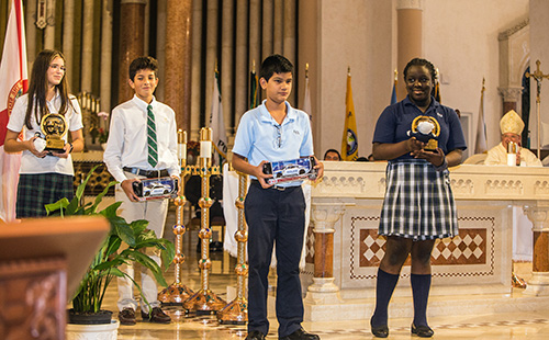 Sunny Isles Police Chief Fred Maas presented two students each from St. Patrick and St. Lawrence schools with gifts during the Blue Mass: police cars for the boys and teddy bears named Freddy for the girls. From left, holding their gifts: St. Patrick seventh grader Carolina Heimes, 12, and eighth grader, Samuel Vasquez, 13; and St. Lawrence eighth grader Julian Quintero, 13, and seventh grader, Leyla Masson, 12.