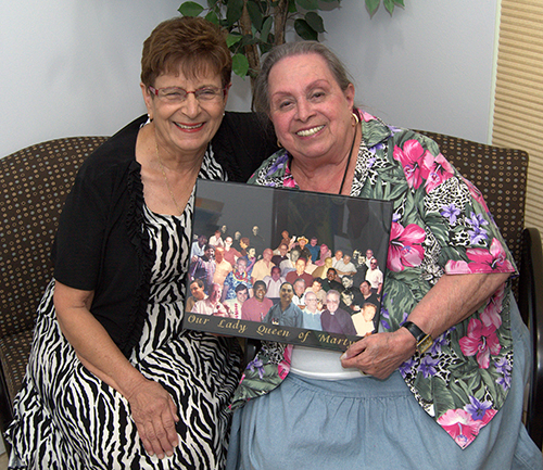 "Regina Medina, left, and Jessie Chiccone hold a composite photo of former pastors at Our Lady Queen of Martyrs. The two women met four decades ago, and ""We've been huggers ever since,"" Chiccone said."