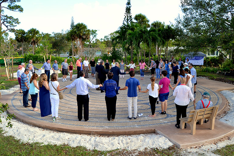 Catholics and Lutherans join hands in the Lord's Prayer at the dedication of the new labyrinth at MorningStar Renewal Center in Pinecrest.