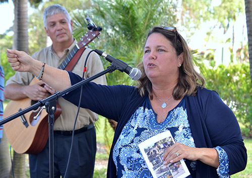 Susan DeFerrari, director of ministry at MorningStar renewal Center in Pinecrest, emcees during the dedication of its new labyrinth. Behind her on guitar is her husband, Michael.
