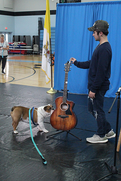 Archbishop Coleman Carroll High's mascot, Archie the bulldog, gets a sniff of country music singer Dylan Schneider's guitar.