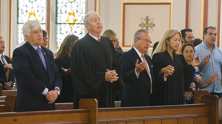 From left: Judge Federico Moreno, Judge Vance Salter, and George Mencio, with his wife, Judge Cecilia Altonaga, pray the Our Father during the Red Mass.