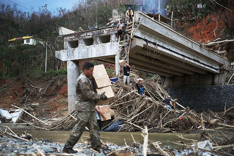 Members of the U.S. Army 1st Special Forces Command deliver boxes of M.R.E's and water up a makeshift ladder to people that were cut off after the bridge collapsed when Hurricane Maria swept through the island on October 5, 2017 in Utuado, Puerto Rico. The neighborhood was cut off from help for about 2 weeks and there is still a need for basic life necessities after the category 4 hurricane passed through.