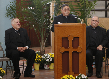 Newly named Auxiliary Bishop for the Archdiocese of Miami Father Enrique Delgado speaks at a press conference. With him, on the left, Archbishop Thomas Wenski, and on the right, Bishop Peter Baldacchino.