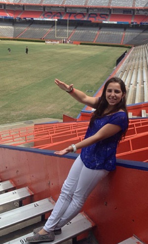 Florida Catholic newspaper freelancer and intern Christy Piña does the Florida Gator chomp at the Ben Hill Griffin Stadium, also known as