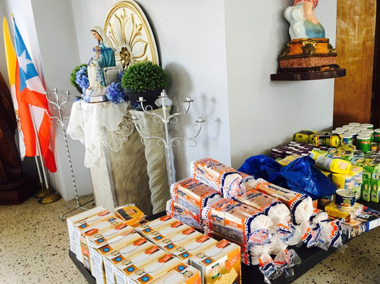 Photo of food and other provisions purchased by members of San Francisco Javier Parish in Barrio Navarro, Gurabo, Puerto Rico, for sharing with the community. At rear, the flags of the Vatican and Puerto Rico and the image of the island's patroness, Our Lady of Divine Providence.