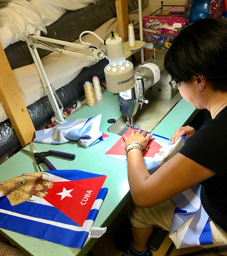 Lucia Vallejo, encargada y maestra del taller de costura del Centro La Salle, en Homestead cose las estolas con la imagen de la Virgen de la Caridad sobre la bandera cubana.