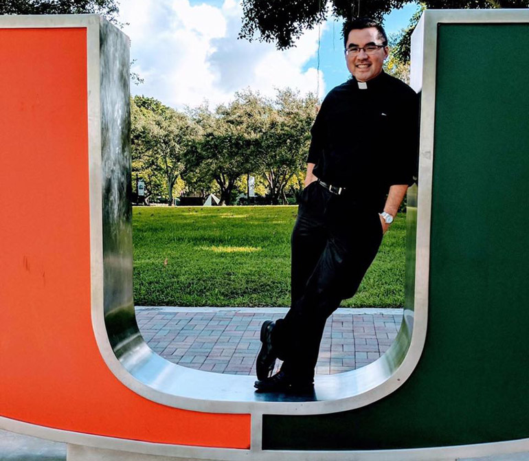 Going back to the U: Father Phillip Tran, a 2008 alumnus, poses on the iconic orange and green U at the University of Miami. Father Tran is the school's new full time Catholic Campus ministry chaplain.