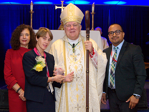 Archbishop Wenski presents one of two Esperanza Ginoris awards to Ana Olaso Stanham during the 2017 Archdiocesan Catechetical Conference. To the left and right are Kim Pryzbylski, archdiocesan director of faith formation, and Peter Ductram, archdiocesan director of catechesis.