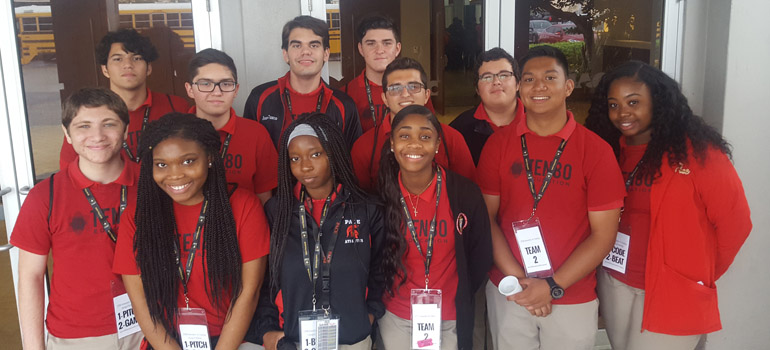 Students from Msgr. Edward Pace High pose before attending TEN80 Education's STEM Innovators-in-Training Workshop at the Miami Airport Convention Center. Top row, from left: Jacob Moral, Javier Bacerio, Joseph Cusco, Kyle Hancock, Jon Rodriguez, and Marcus Lora; bottom row, from left: Thomas Balaki, Raven Jacques, Quinteria Dandy, Rose Delva, Keanu Orfano, and Kai Cooper.