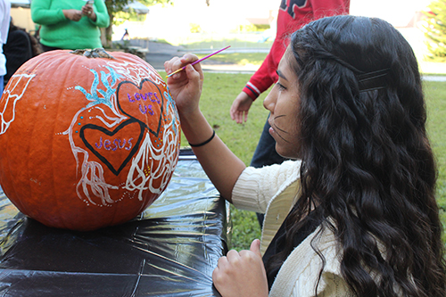 No carving here, only a blank canvas with endless opportunities: eighth-grader Joanna Rosales puts the finishing touches on her team's pumpkin for the Light of the World carving and decorating contest at St. Michael the Archangel School.