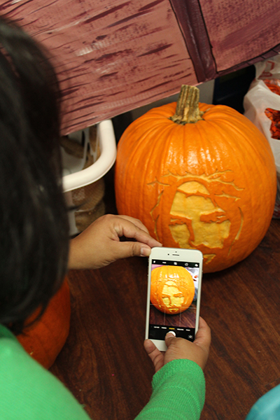 Archdiocese of Miami Media Coordinator & Digital Media Specialist Maria Alejandra Rivas gets a shot of a pumpkin-carved Christ for social media.