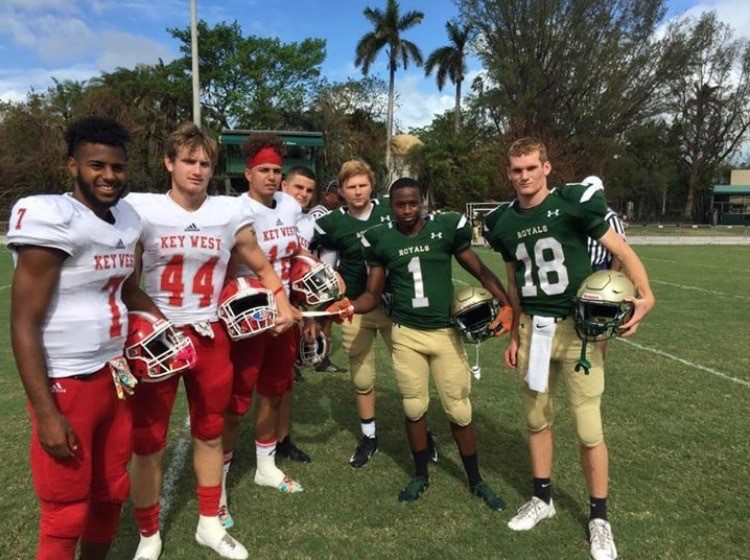 Immaculata-La Salle students Michael Matamoros, Cameron Ryals, and Daniel Burke, at right, present Key West High players with a ,000 disaster relief donation prior to their game last month.