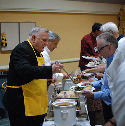 Archbishop Thomas Wenski helps serve Thanksgiving dinner to members of St. John Neumann's Men's Club Nov. 6.